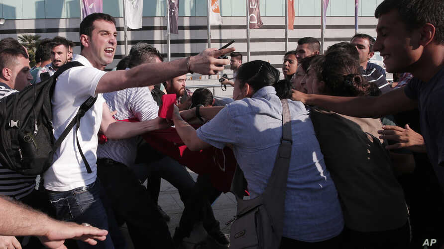 Turkish plainclothes police, left, push back protesters in Istanbul as they tried to stage a march to denounce the deaths in an explosion Monday in the Turkish town of Suruc near the Syrian border, July 21, 2015.