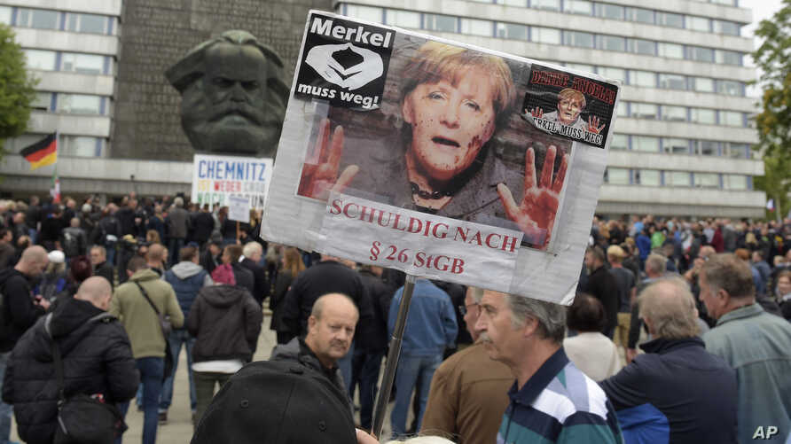 """A protester holds up a poster with a photo of German Chancellor Angela Merkel declaring her """"Guilty"""" at an anti-migrant rally in Chemnitz, eastern Germany, Sept. 1, 2018."""