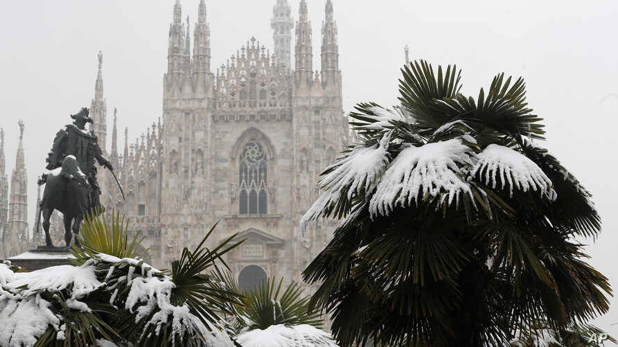 FILE - Palm trees are dusted in snow after a snowfall in front of Milan's Gothic Cathedral, Italy, March 2, 2018. New U.S. weather data shows that the Arctic just finished its warmest winter on record, with plenty of open water where the ocean normal