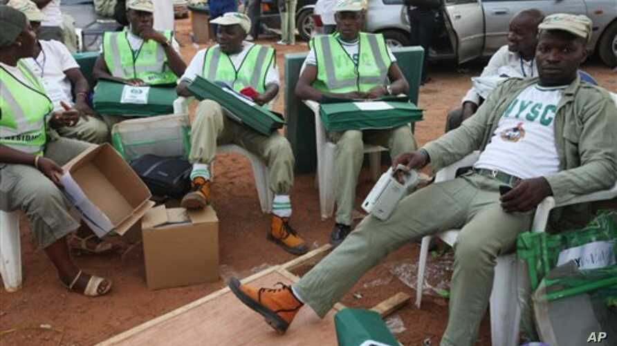 Electoral officials wait for ballot material at the distribution center  in Ibadan, Nigeria, Saturday, April 2, 2011