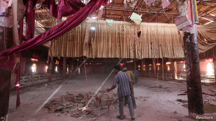Men remove rubble from a damaged wedding hall after a suicide attack on a Kurdish wedding in Hasaka city, Syria, Oct. 4, 2016.
