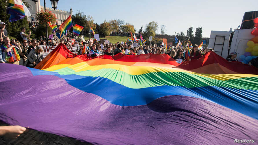 "Participants display a large rainbow flag at the ""Equality Parade"" rally in support of the LGBT community in Lublin, Poland, Oct. 13, 2018. More than 200 Polish schools had planned to take part in ""Rainbow Friday,"" an anti-discrimination event set fo"