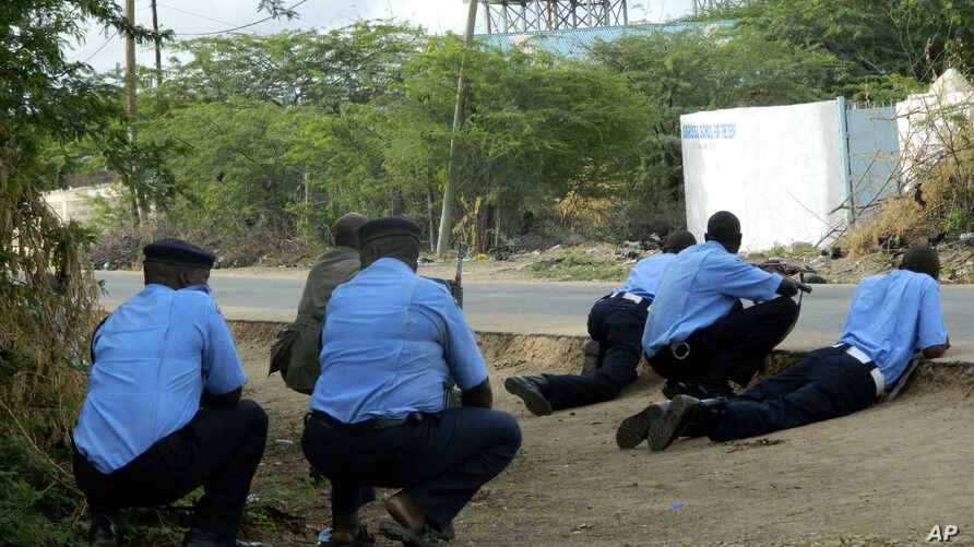 Kenyan police officers take cover outside the Garissa University College during an attack by gunmen in Garissa, Kenya, Thursday, April 2, 2015.