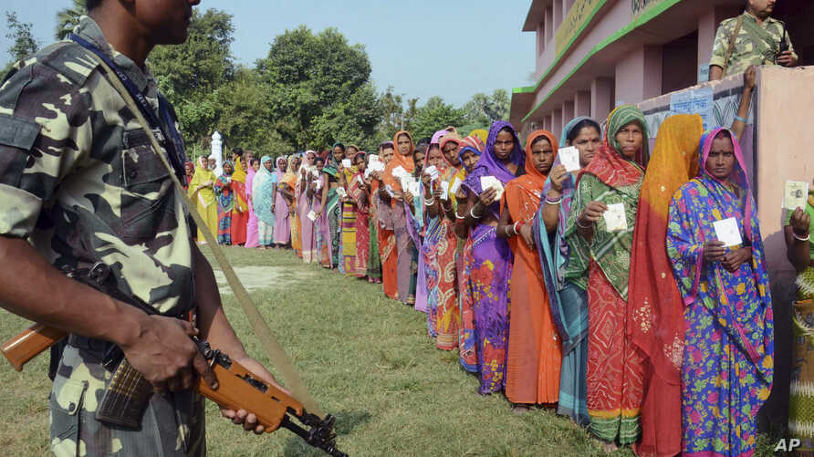 Indian security personnel guard as women voters stand in a queue to cast their votes at a polling station during the first of the five phase voting for state legislative assembly at Mahmoodpur village, in Samastipur district of India's eastern state