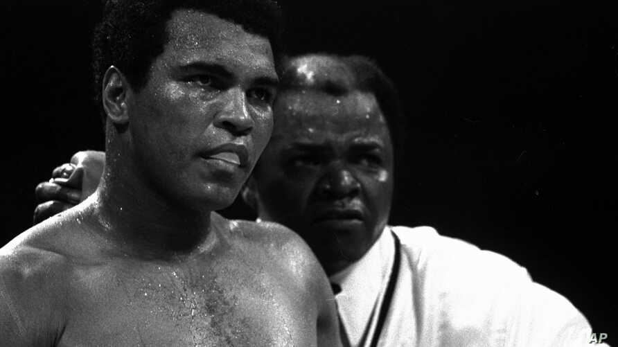 Muhammad Ali stands with longtime trainer Bundini Brown after Ali became the first man to win the world heavyweight championship three times at the Superdome in New Orleans, September 15, 1978.