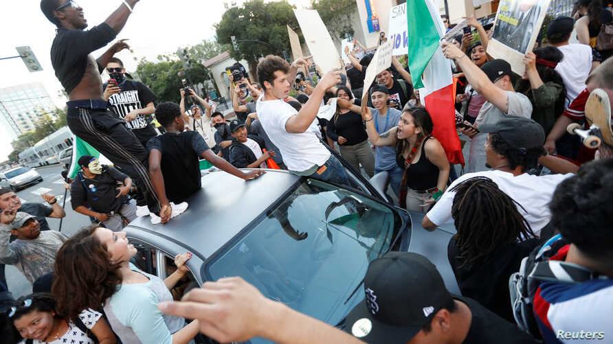 Demonstrators chant around a car during a demonstration against Republican U.S. presidential candidate Donald Trump after his campaign rally in San Jose, California, June 2, 2016.