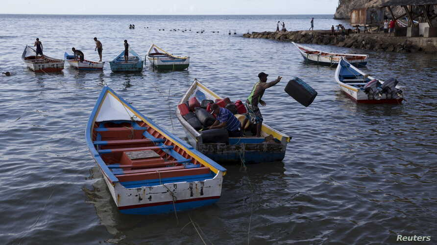 Men unload containers from a boat in the bay of Rio Caribe a town near caribbean islands, in the eastern state of Sucre, Venezuela, Oct. 29, 2015.