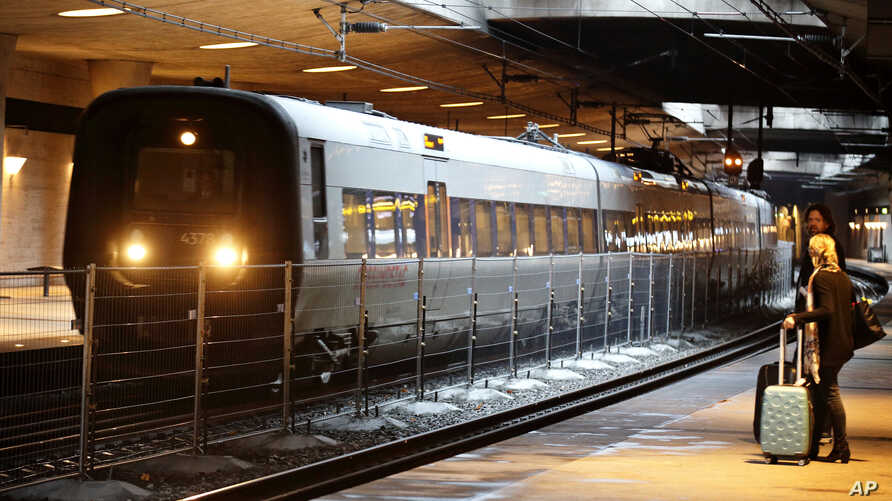 FILE - A temporary fence is erected between tracks at the train station to prevent illegal migrants entering Sweden, at Copenhagen International Airport in Kastrup, DEc. 23, 2015.