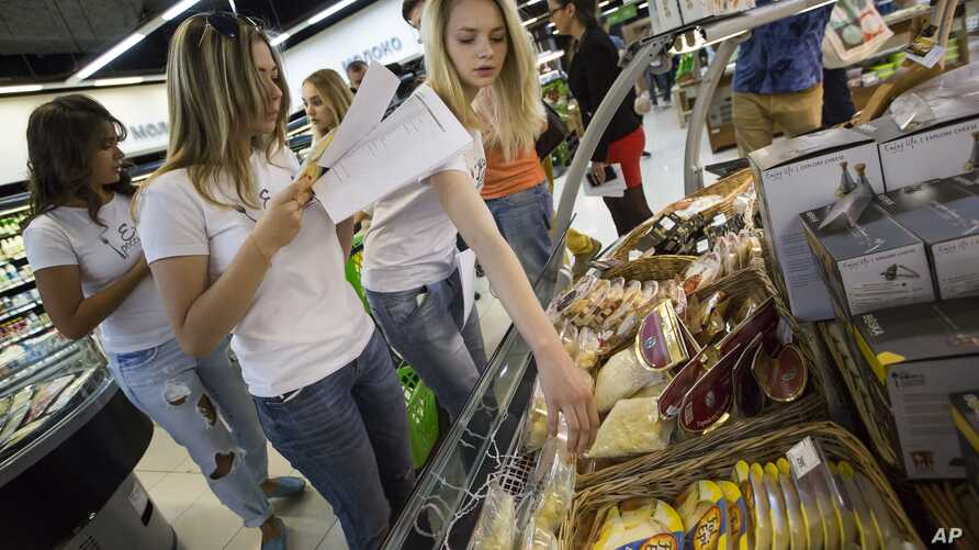 "FILE - A group of activists, members of the ""Eat Russian Food"" movement, check food at a store in Moscow, Russia, Aug. 4, 2015."