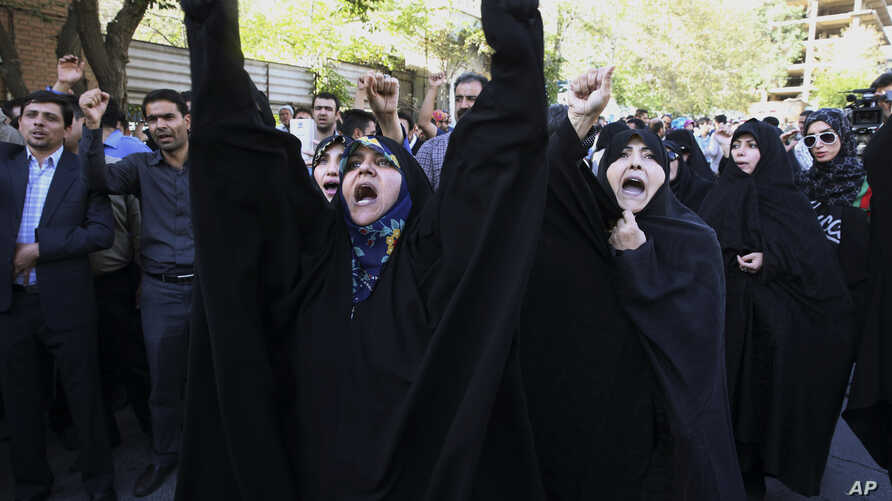 Iranian protesters chant slogans in front of the Saudi Arabian Embassy in Tehran, Iran, Sunday, Sept. 27, 2015, during a gathering to blame the Arab country for a deadly stampede on Thursday that killed more than 700 pilgrims. Iran's hajj agency on S