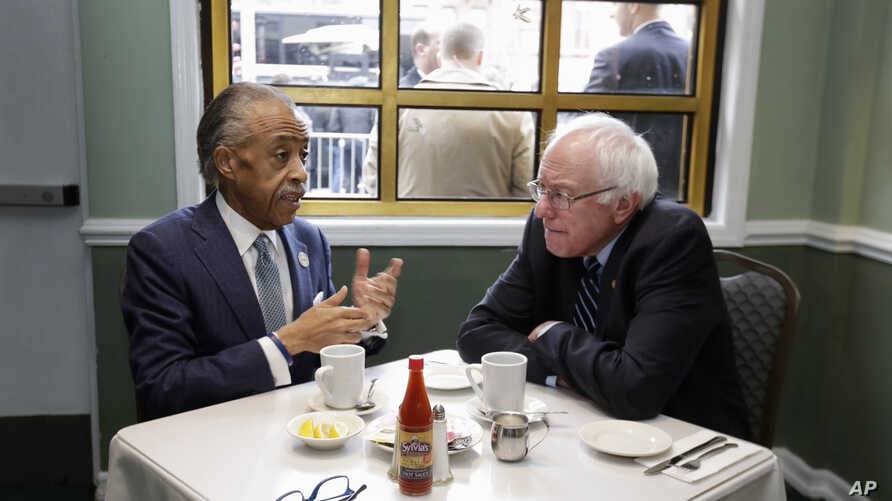 The Rev. Al Sharpton (l) talks with Democratic presidential candidate Sen. Bernie Sanders, as they sit down for a breakfast meeting at Sylvia's Restaurant, Feb. 10, 2016, in the Harlem neighborhood of New York.