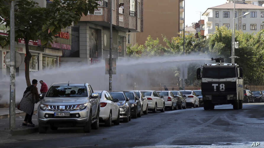 Police use water cannons against pro-Kurdish Peoples' Democratic Party members as they protest the detention of Gultan Kisanak, Diyarbakir mayor, and Co-mayor Firat Anli, in Diyarbakir, Turkey, Oct. 26, 2016.
