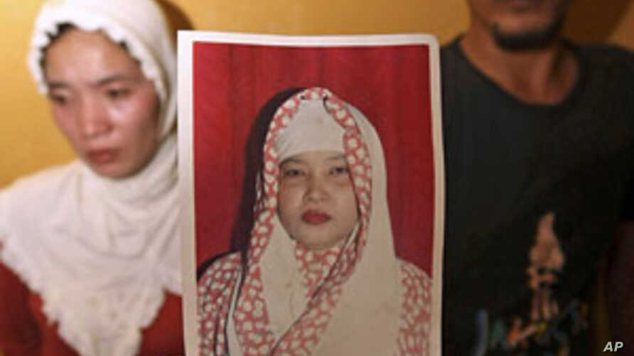 Irwan Setiawan (R) along with his sister Evi Kurniati, holds a picture of his mother, Ruyati Binti Sapubi.  The 54-year-old Indonesian maid was beheaded on Saturday, convicted of murdering her Saudi employer, June 19, 2011