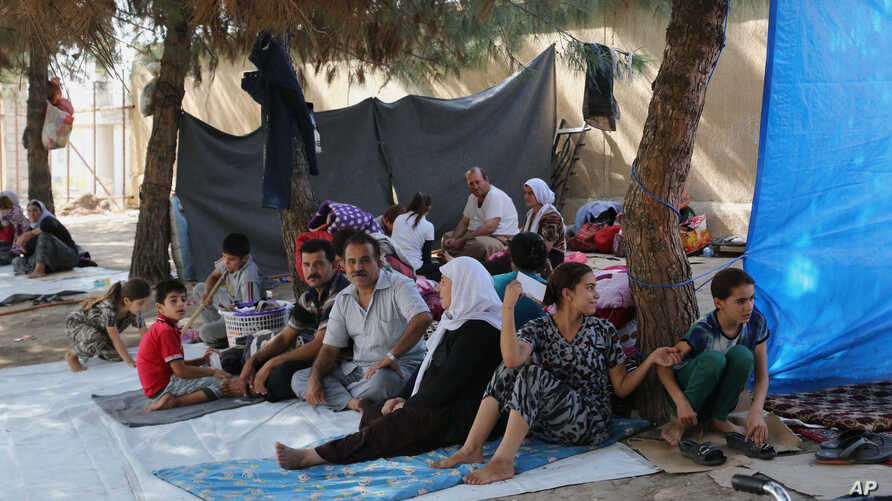 Displaced Iraqis from the Yazidi community gather at a park near the Turkey-Iraq border at the Ibrahim al-Khalil crossing, as they try to cross to Turkey, in Zakho, 475 km northwest of Baghdad, Aug. 15, 2014.