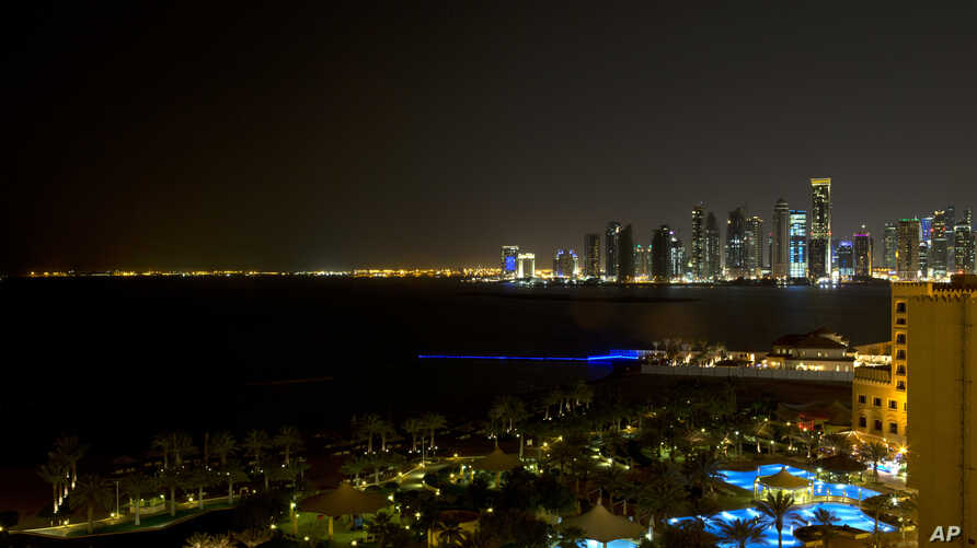 FILE - The skyline of Doha, Qatar, is seen at night from the St. Regis Hotel.
