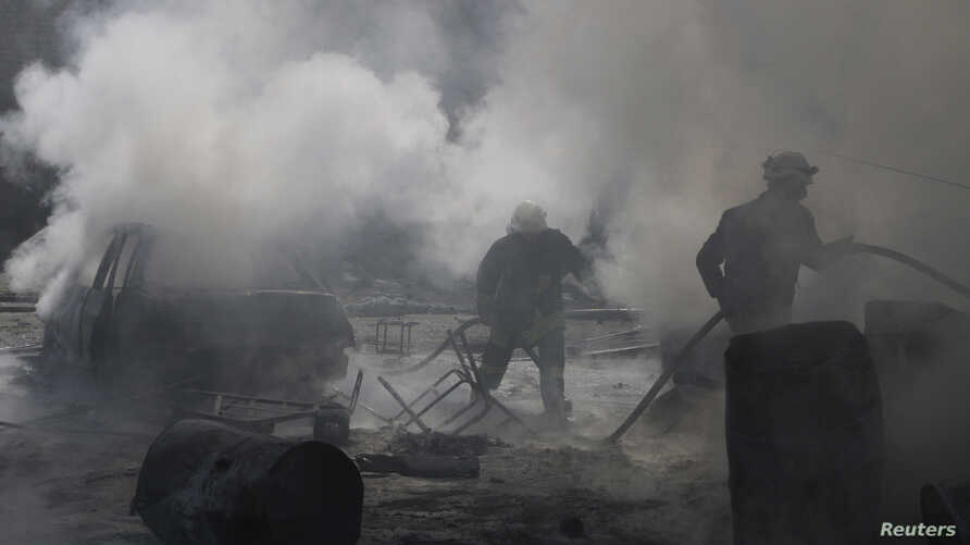 Civil defense members try to put out a fire at a site hit by what activists said was a barrel bomb dropped by forces loyal to Syria's President Bashar al-Assad in the Qadi Askar neighborhood of Aleppo, March 5, 2015.