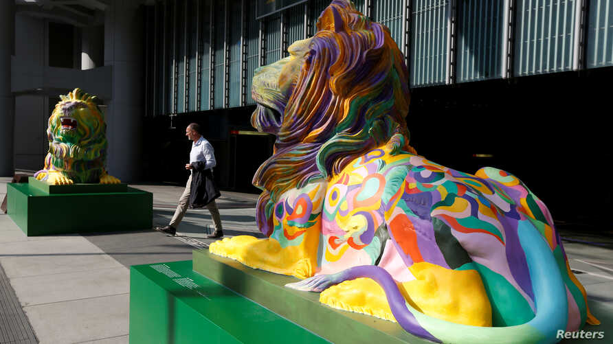 """FILE - """"Stephen"""" (L) and """"Stitt"""", the two lions in rainbow colors to show support for the LGBT (lesbian, gay, bisexual and transgender) community, are newly displayed at HSBC's main branch in Hong Kong, Dec. 7, 2016."""
