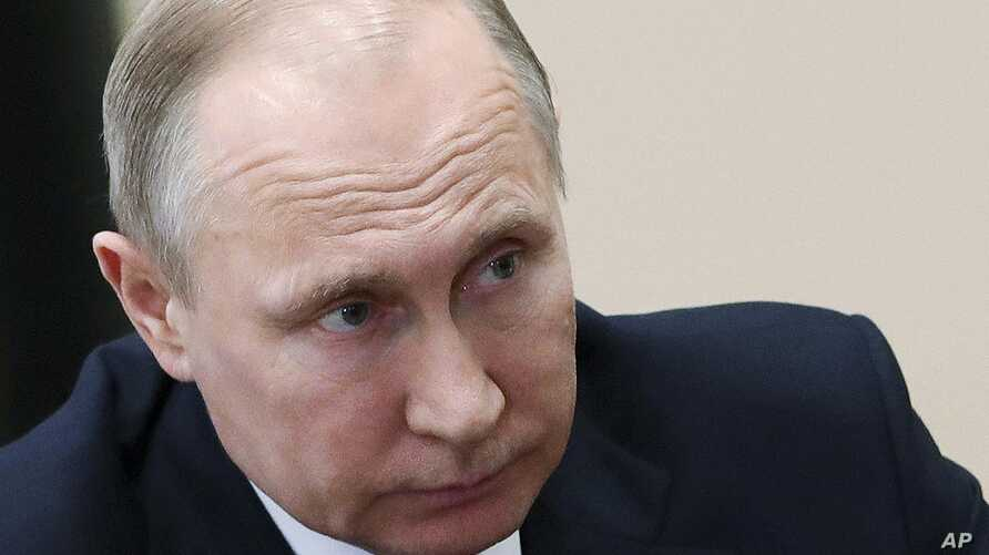Russian President Vladimir Putin listens during a meeting in Moscow, Russia, Friday, April 13, 2018. The Kremlin says Russian President Vladimir Putin and French President Emmanuel Macron have agreed to coordinate their actions to avoid further milit...