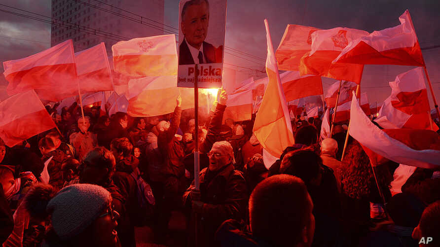 Demonstrators burn flares and wave Polish flags during the annual march to commemorate Poland's National Independence Day in Warsaw, Poland, Nov. 11, 2017. Thousands of nationalists marched in Warsaw on Poland's Independence Day holiday, taking part