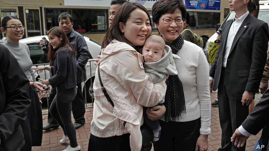 Hong Kong's chief executive elect Carrie Lam (center right) poses with local residents in Hong Kong, March 27, 2017.