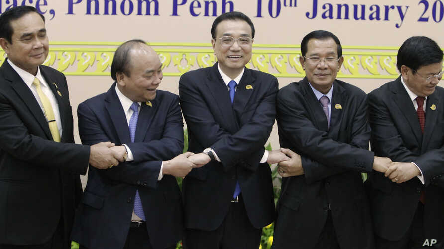 China's Premier Li Keqiang, center, shakes hands with his counterpart, Nguyen Xuan Phuc of Vietnam, Prayuth Chan-o-cha, prime minister of Thailand, Hun Sen of Cambodia, and Thongloun Sisolith of Laos, in Phnom Penh, Jan. 10, 2018.