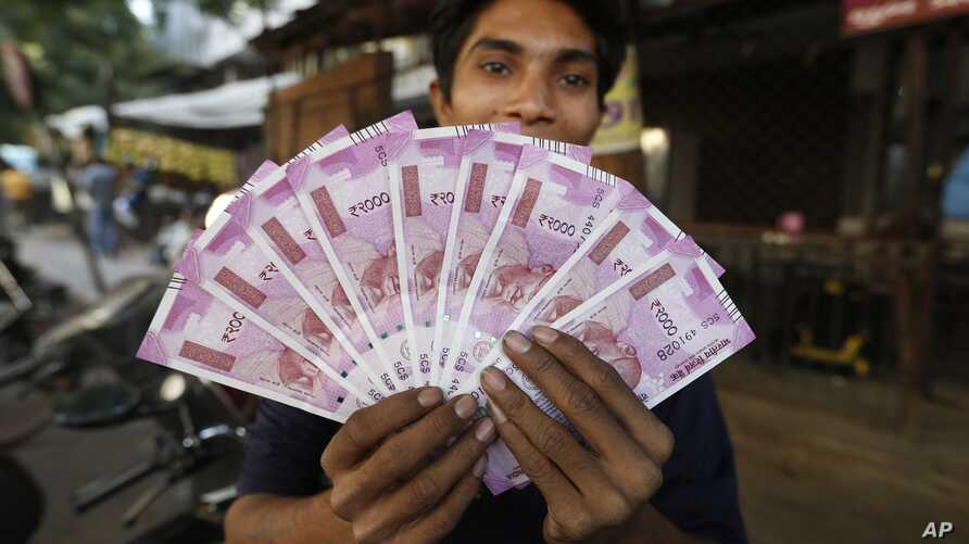 FILE - An Indian man displays new currency notes of 2000 Indian rupee in Ahmadabad, India, Nov. 11, 2016. The sudden withdrawal of 86 percent of India's currency has left cash in short supply, retail sales stumbling and wholesale markets in turmoil.