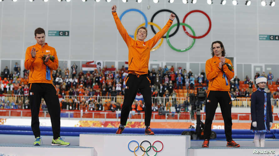 Second-placed Sven Kramer (L) of the Netherlands and his compatriot third-placed Bob de Jong (R) applaud winner Jorrit Bergsma of the Netherlands, during the flower ceremony for the men's 10,000 meters speed skating race at the Adler Arena, in the So