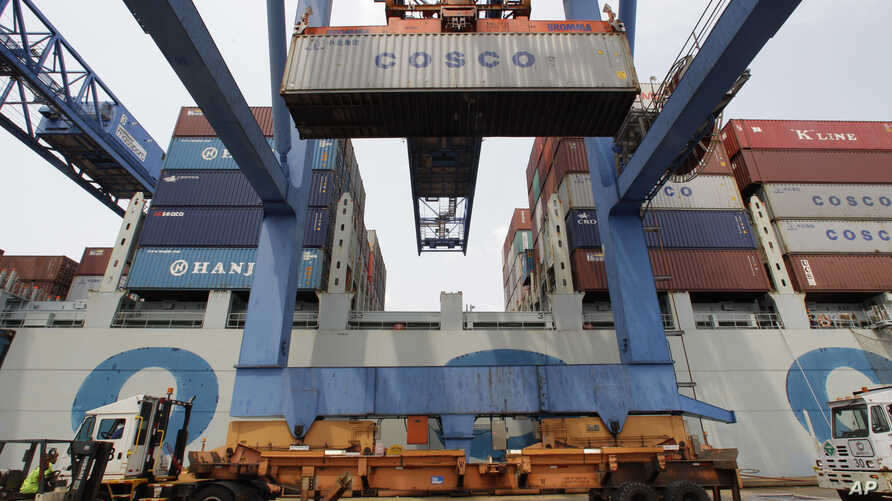 In this Friday, July 13, 2012, photo, a container ship from China is offloaded at Massport's Conley Terminal in the port of Boston.
