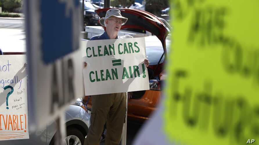 FILE - Paul Gipe protests before the first of three public hearings on the Trump administration's proposal to roll back car-mileage standards in a region with some of the nation's worst air pollution, in Fresno, Calif., Sept. 24, 2018.
