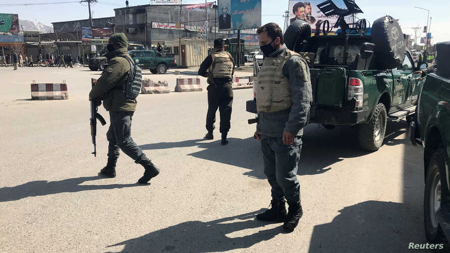 Policemen keep watch near the side of an attack in Kabul, Afghanistan, March 7, 2019.