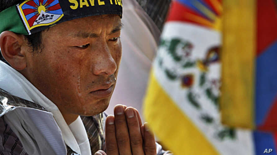 Tears roll down the cheeks of a Tibetan exile as he listens to a speaker during a protest outside the Chinese Embassy on the first day of Tibetan New Year, in New Delhi, India,  February 22, 2012.
