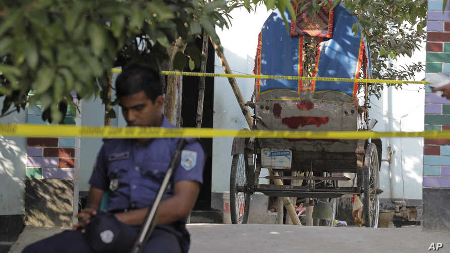 A Bangladeshi policeman sits next to a cycle rickshaw, on which Japanese citizen Kunio Hoshi was reported to be traveling while he was killed at Mahiganj village in Rangpur district, 300 kilometers (185 miles) north of Dhaka, Bangladesh, Oct. 4, 2015