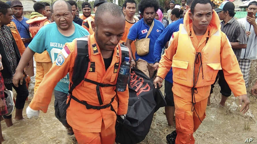 At least 50 people were killed and 59 injured in Papua Province, Indonesia, March 17, 2019. In this photo provided by National Search and Rescue Agency, the agency's personnel and police carry the body of one flood victim at Sentani, the hardest-hit