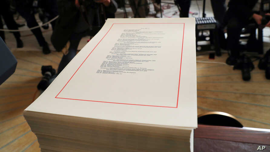 FILE - A copy of the $1.3 trillion spending bill is stacked on a table in the Diplomatic Room of the White House in Washington, March 23, 2018.