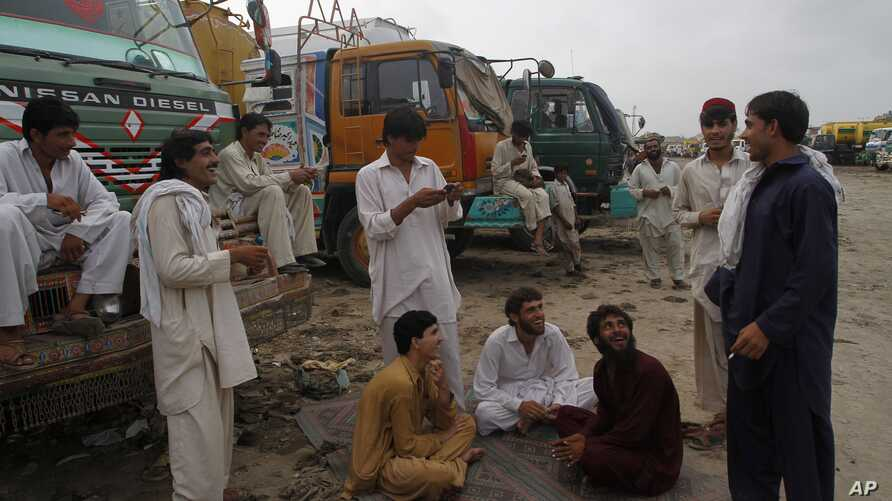 Drivers of oil tankers, which were used to transport NATO fuel supplies to Afghanistan, gather next to their tankers parked in Karachi, Pakistan, July 4, 2012