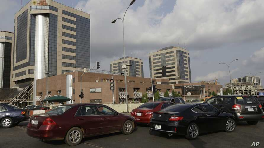 FILE- Cars queue in front of the Nigerian National Petroleum Corporation headquarters to buy fuel in Abuja, Nigeria, May 26, 2015.