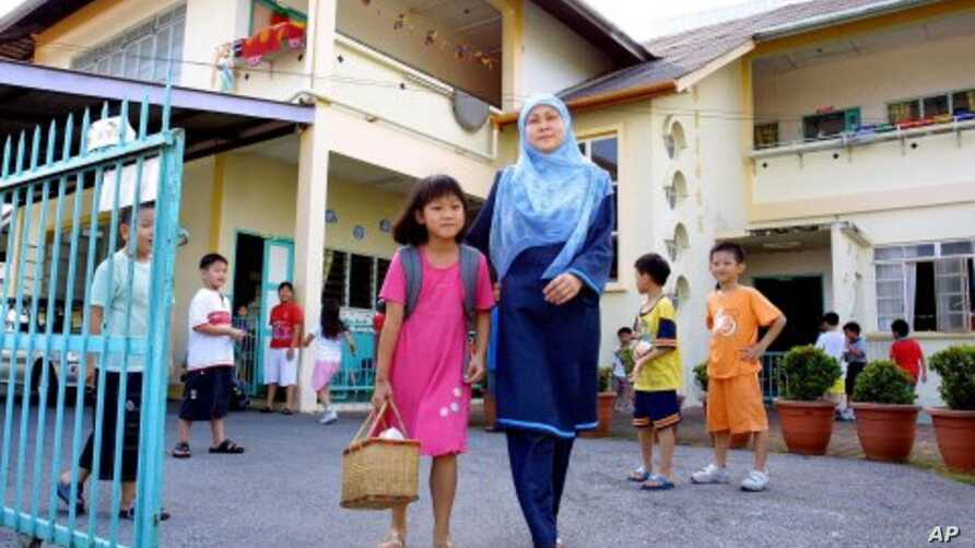 A Malaysian mother picks her daughter up from a pre-school after it was closed in Kuching, the capital of Malaysia's Borneo state of Sarawak. (File Photo)