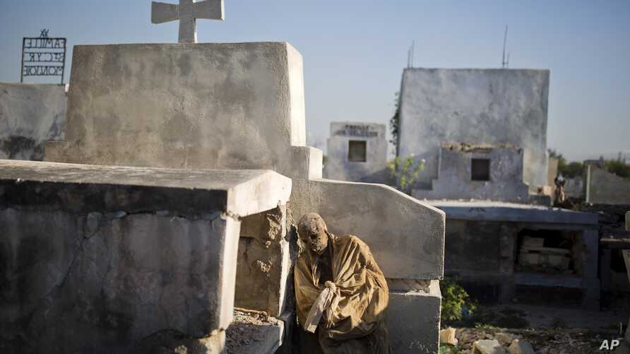 FILE - The remains of an exhumed corpse leans against its grave before being taking away to a mass grave in the national cemetery in Port-au-Prince, Haiti, March 29, 2017. Many bereaved Haitians go into a lifetime of debt to send off deceased relativ