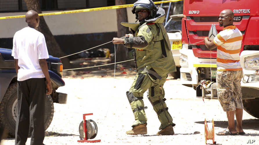 A member of a bomb disposal team prepares the scene before checking the bodies of three women who were shot dead by police, outside the central police station in the coastal city of Mombasa, Kenya Sunday, Sept. 11, 2016. The three women were killed b