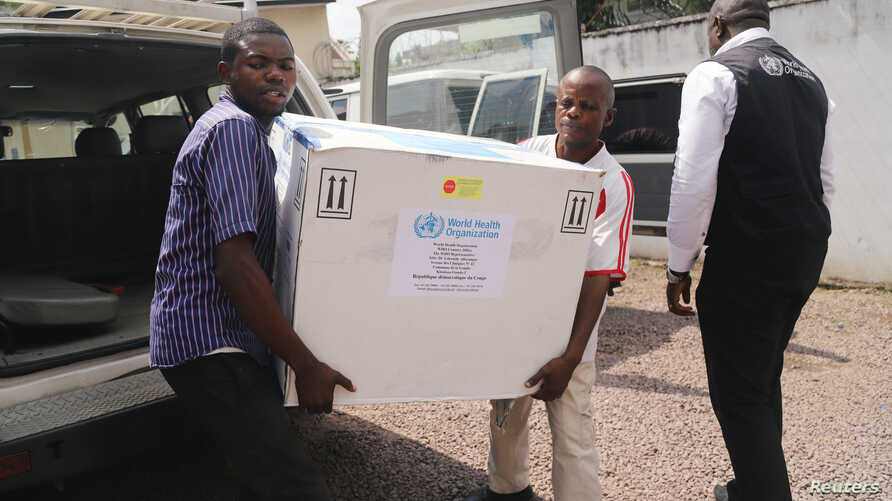 Congolese Health Ministry officials carry the first batch of experimental Ebola vaccines in Kinshasa, Democratic Republic of Congo, May 16, 2018.