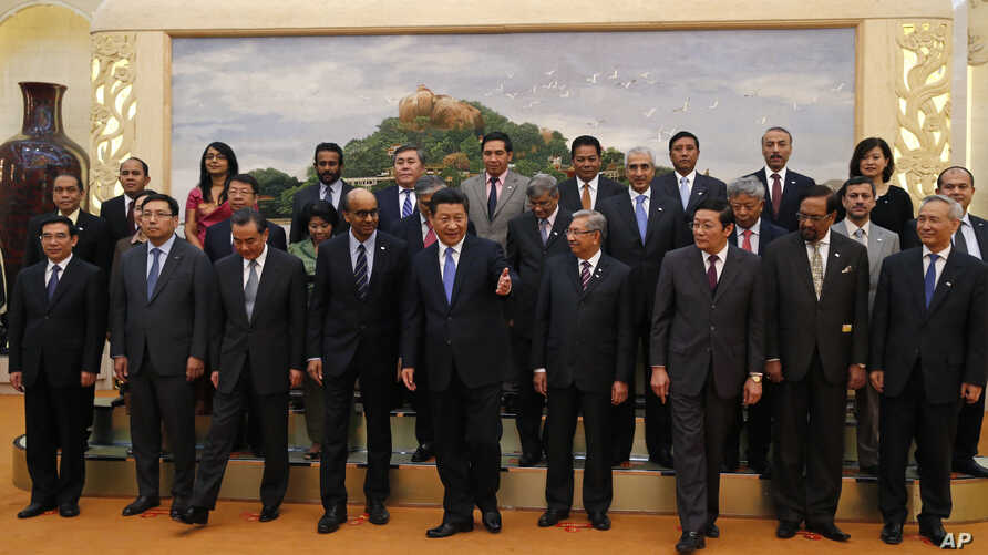 Chinese President Xi Jinping, center, shows the way to the guests who attended the signing ceremony of the Asian Infrastructure Investment Bank at the Great Hall of the People in Beijing, Oct. 24, 2014.