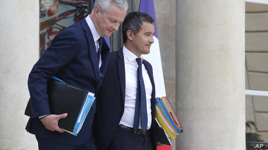 French Finance Minister Bruno Le Maire, left, and French Budget Minister Gerald Darmanin leave the Cabinet meeting at the Elysee Palace in Paris, France, Aug. 23, 2018.
