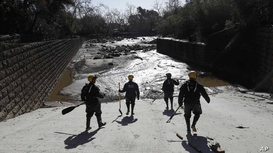 Members of the Los Angeles County Fire Department Search and Rescue crew walk toward flooded waters in Montecito, Calif., Jan. 10, 2018.