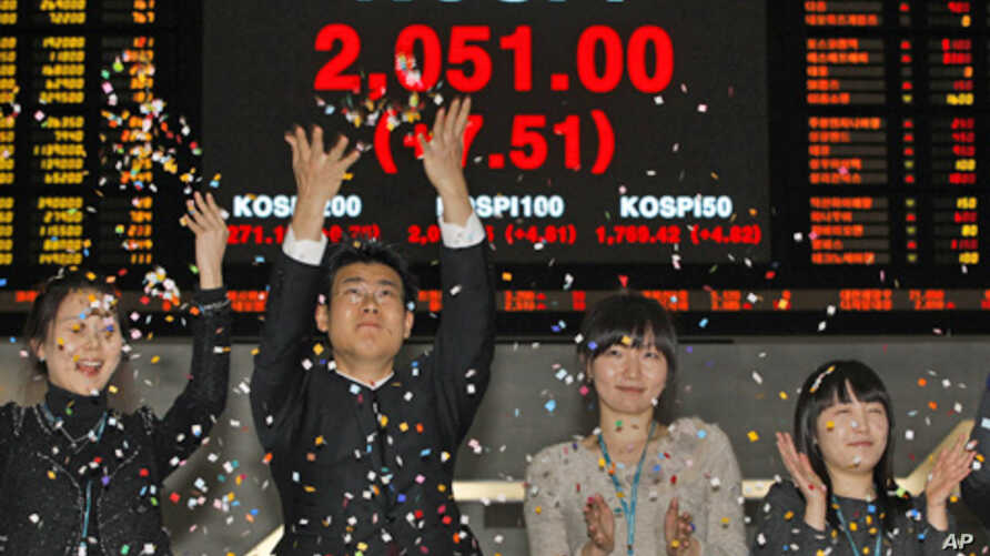 Employees of the Korea Exchange applaud in front of the final stock price index for the ceremonial closing of the 2010 stock market at the Korea Exchange, Seoul, 30 Dec 2010