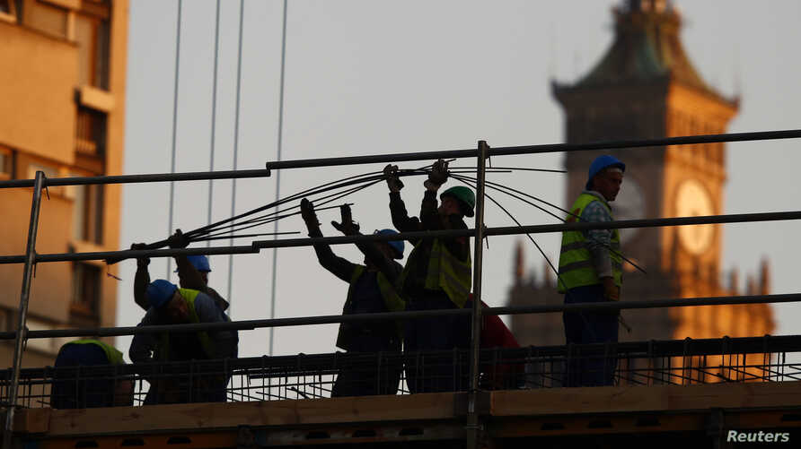 Laborers work at a construction site in Warsaw, Nov. 5, 2014.