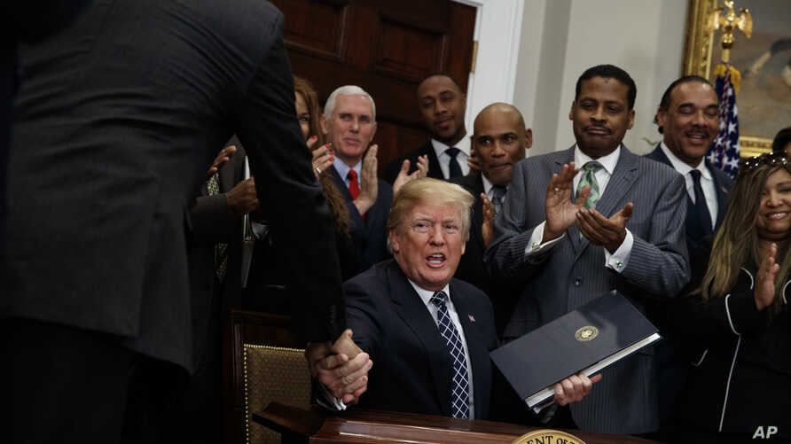 President Donald Trump shakes hands during an event to honor Dr. Martin Luther King Jr., in the Roosevelt Room of the White House, Jan. 12, 2018, in Washington.