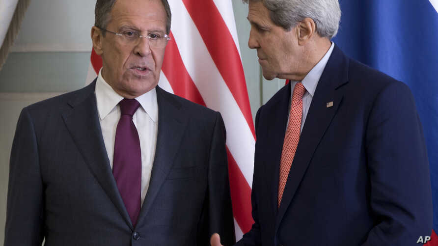 U.S. Secretary of State John Kerry talks with Russian Foreign Minister Sergey Lavrov, left, at the Chief of Mission Residence in Paris, France, Oct. 14, 2014.