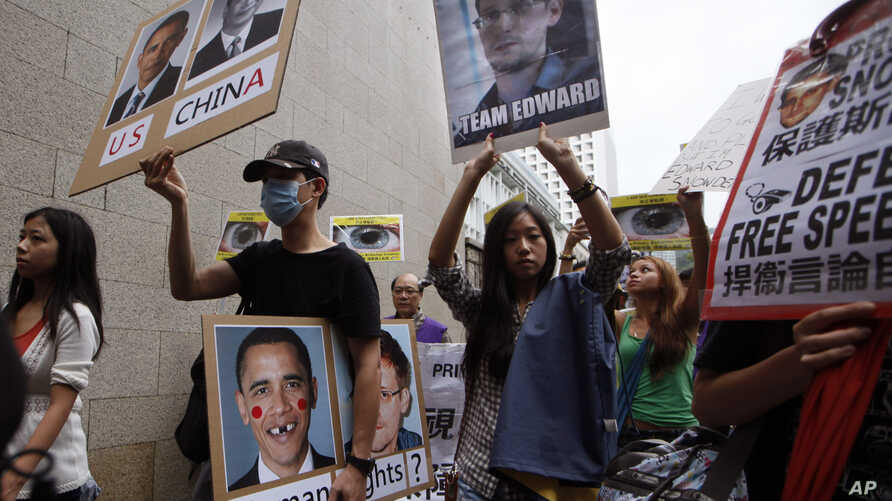 Supporters of Edward Snowden, a former CIA employee who leaked top-secret information about U.S. surveillance programs hold placards as they march to the Consulate General of the United States in Hong Kong Saturday, June 15, 2013.