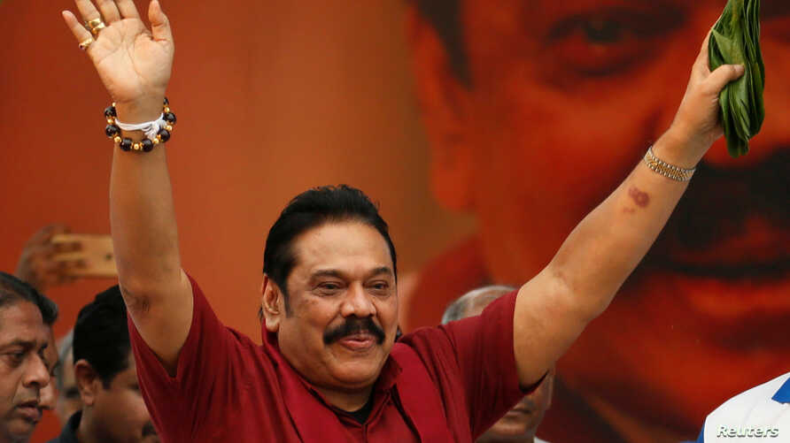 "Sri Lanka's former president Mahinda Rajapaksa waves at his supporters as he arrives at a protest rally to launch a plan to topple the current government, accusing it of failing in its ""management and development of the country"" in Colombo, Sri Lanka"