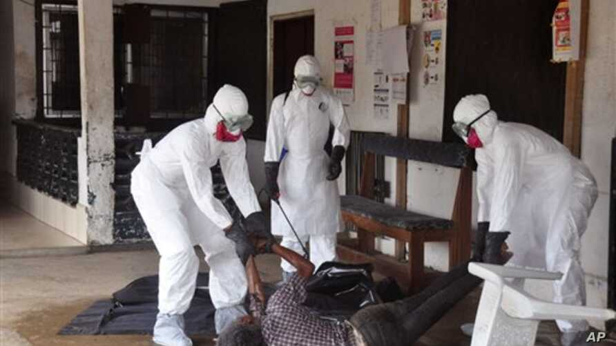 Health workers in protective gear move the body of a person that they suspect died from the Ebola virus in Monrovia, Liberia.